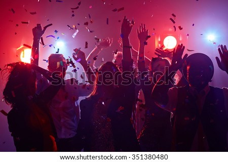Young people dancing in night club - stock photo