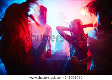 Young people dancing in nightclub - stock photo