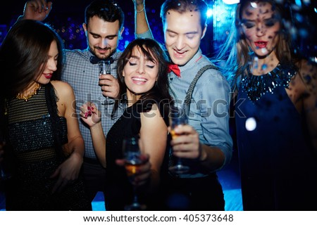 Young people dancing together in nightclub - stock photo