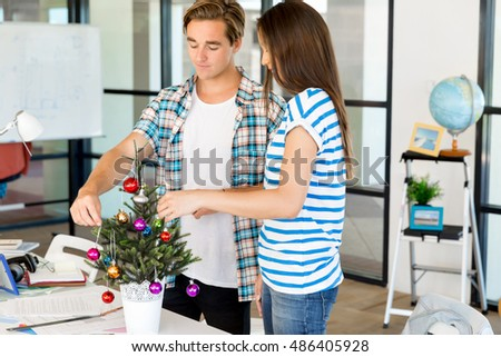 Young people decorating christmas tree in office
