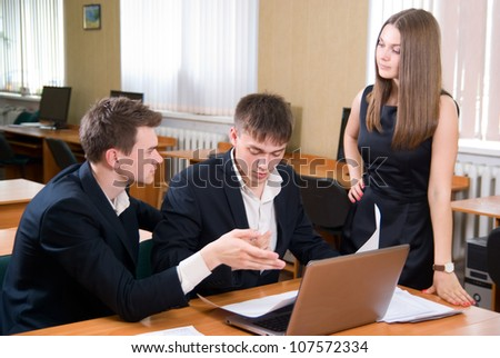 Young people discuss fresh project. The guy shows a hand on the laptop - stock photo