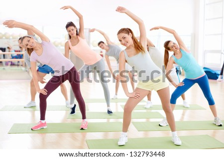 Young people do exercises in the gym - stock photo