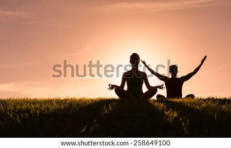 Young people do yoga outdoors - stock photo