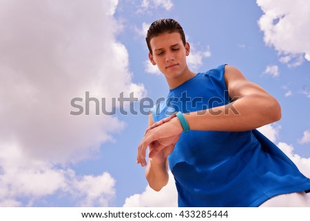 Young people doing sport activities, man runner jogging using fit watch.