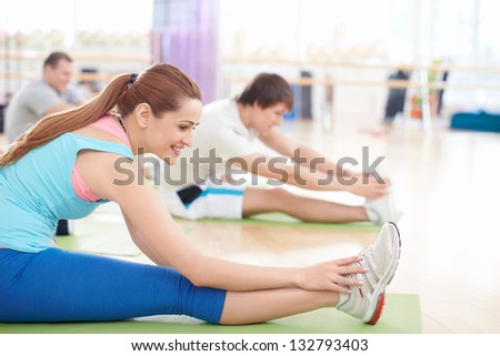 Young people doing stretching in the gym