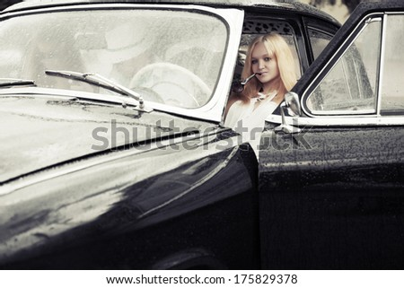 Young people driving retro car in the rain - stock photo