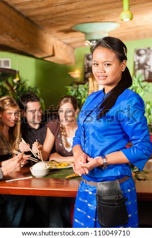 Young people eating in a Thai restaurant; the waitress brings the dishes, rice and others - stock photo