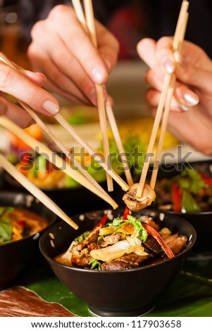 Young people eating in a Thai restaurant, they eating with chopsticks, close-up on hands and food - stock photo