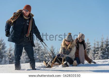 Young people enjoy sunny winter day sledge man pulling girlfriends - stock photo