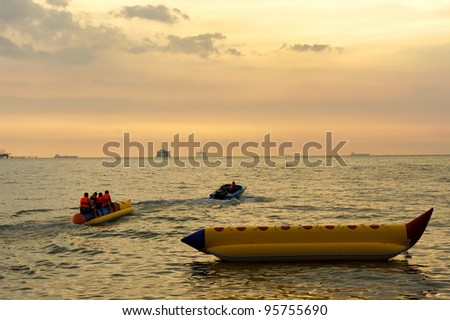 Young people enjoying a ride on a banana boat at tropical beach during sunset. - stock photo