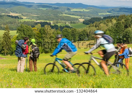 Young people enjoying scenic view from the mountain on summer weekend - stock photo