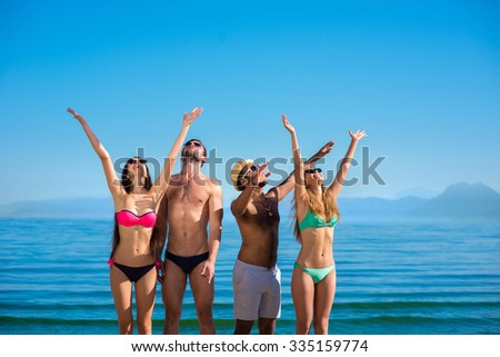 Young people enjoying the holiday on the island. Summer holiday at sea. Guys and girls on the beach. Happy youth. - stock photo