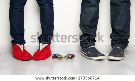 Young people family legs feet standing together, pretty woman,man legs and small baby shoes on light background, family photo close up, pregnancy fragment, maternity - stock photo
