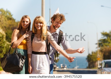 Young people friends hitchhiking on summer vacation. Happy women and man tourists beside road with thumb up gesture having fun. - stock photo