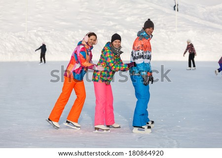 Young people, friends, ice-skating winter and recreation on the frozen lake - stock photo