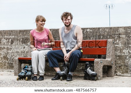 Young people friends in training suit putting on roller skates outdoor. Woman and man sitting on bench.