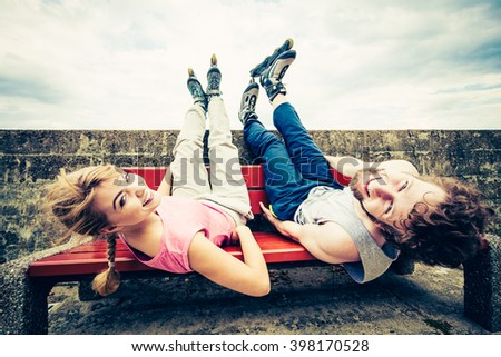 Young people friends in training suit with roller skates. Woman and man relaxing lying on bench outdoor. - stock photo