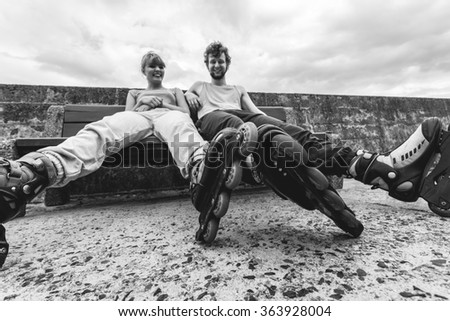 Young people friends in training suit with roller skates. Woman and man relaxing on bench outdoor. - stock photo