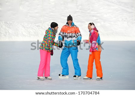 Young people, friends, winter ice-skating on the frozen lake. - stock photo