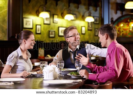Young people having dinner at a restaurant - stock photo