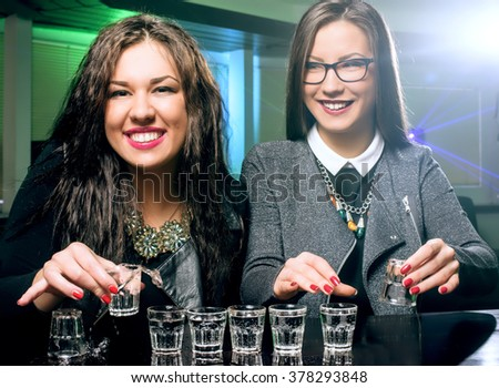 Young people having fun at night club. Two pretty girls drink alcohol - stock photo