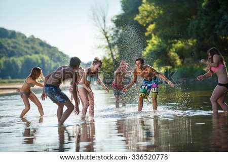 Young people having fun at the beach during a summer day. They are splashing water around them and running out in order to not get wet. They are wearing stylish swimsuits - stock photo