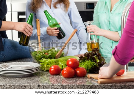 Young people having fun drinking beer and preparing food at home - stock photo