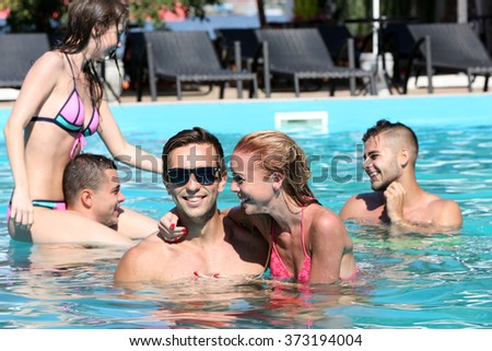 Young people having fun in the swimming pool - stock photo