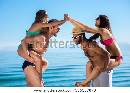 Young people having fun on the beach. In love couple on vacation. In love on the islands. Guys and girls sunbathe. Relax on vacation. - stock photo