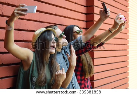 Young people having fun outdoor and making selfie with smart phone against red brick wall. Urban lifestyle, happiness, joy, friends, self photo social network concept. Image toned and noise added. - stock photo