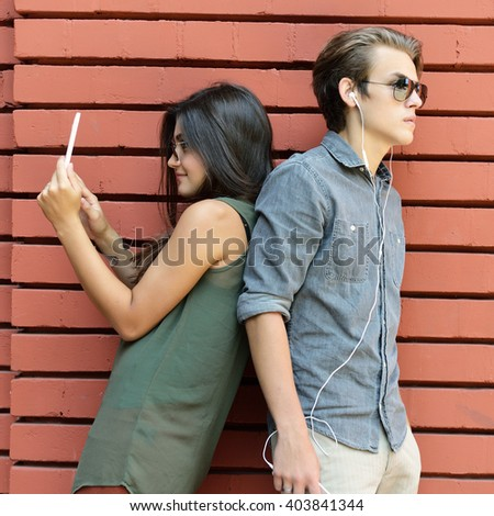 Young people having fun outdoor using gadget like a smartphone and pad against red brick wall. Urban lifestyle, internet and gadget dependence, friends, concept. Image toned and noise added. - stock photo