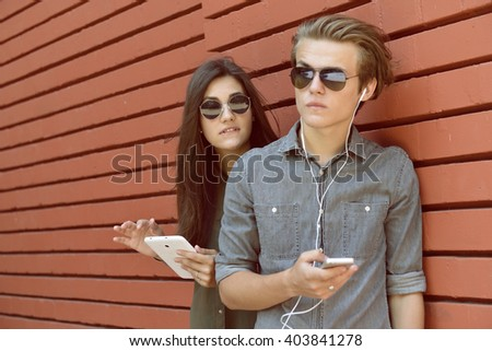 Young people having fun outdoor using gadget like a smartphone and pad against red wall. Urban lifestyle, internet and gadget dependence, friends, social network concept. Image toned and noise added. - stock photo