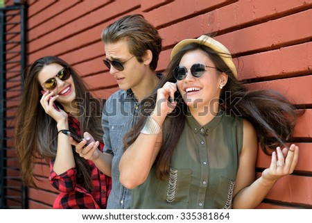 Young people having fun outdoor using smartphones against red brick wall. Urban lifestyle, internet and gadget dependence, friends, social network concept. Image toned and noise added. - stock photo
