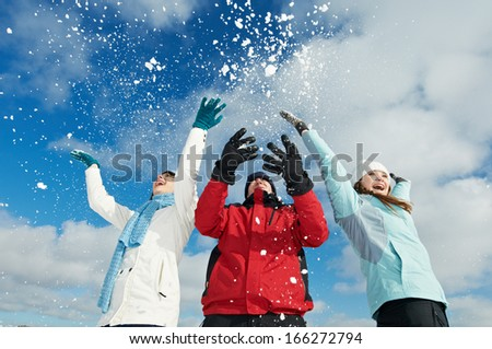 Young people having fun with snow in winter outdoors - stock photo