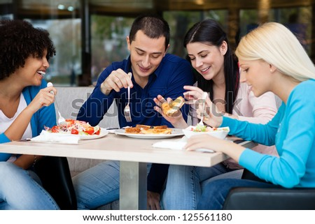 Young people having lunch in restaurant, smiling and talking
