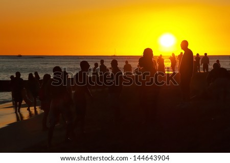 Young people having party on the beach during the sunset - stock photo