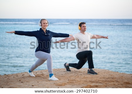 Young people having physical training at the seaside. They doing exercises while enjoying favourite music in wireless headphones