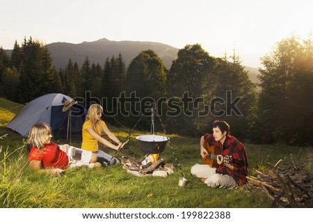 Young people having picnic, man playing guitar - stock photo