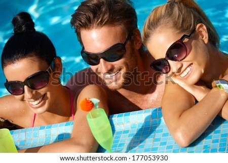 Young people having summer fun in outdoor pool, smiling.