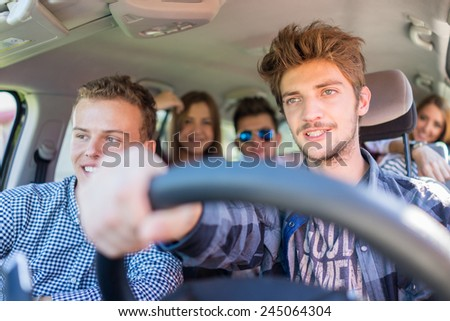 Young people having vacation enjoying fun driving car - stock photo