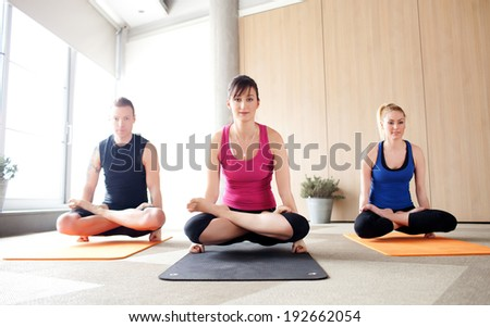Young people holding a scale pose in a yoga class - stock photo