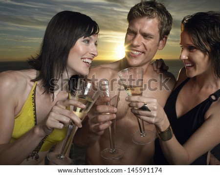 Young people in bathing suits toasting champagne at sunset outdoors