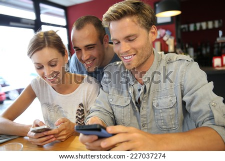 Young people in campus lounge connected on smartphone - stock photo