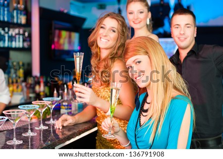 Young people in club or bar drinking champagne and having fun; all are looking into the camera - stock photo