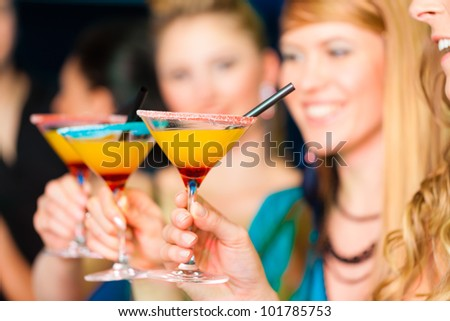 Young people in club or bar drinking cocktails and having fun