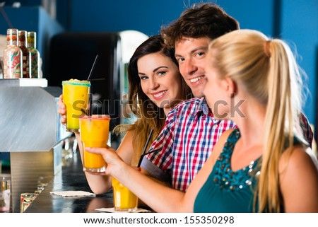 Young people in club or bar drinking cocktails and having fun - stock photo