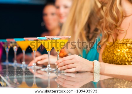 Young people in club or bar drinking cocktails and having fun; close-up on glasses on the bar