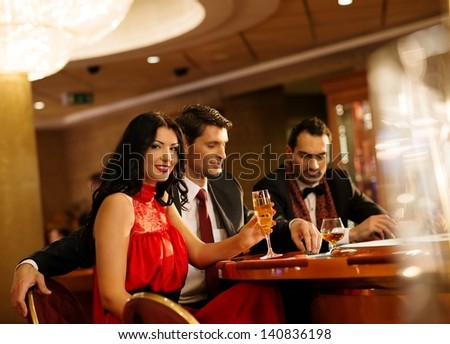 Young people in evening dress behind poker table in a casino - stock photo
