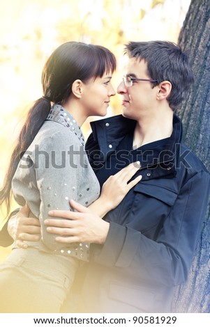 Young people in love looking in each other's eyes; sunny day in the autumn park, golden leaves behind them - stock photo