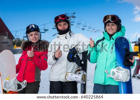 Young people in ski-suits, helmets and ski goggles thumbs-up while standing with snowboards near the fence in a ski-resort in winter period